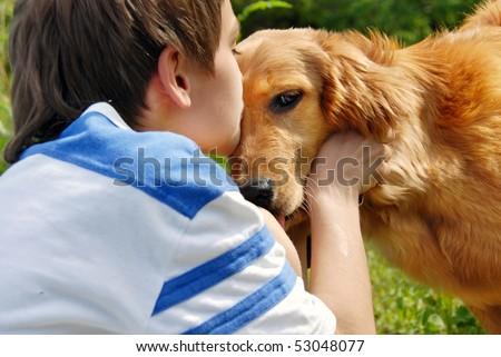 little boy kissing golden retriever dog closeup - stock photo