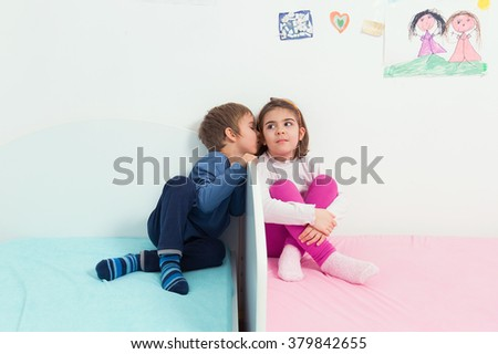 Little boy kissing his sister while playing in their room - stock photo
