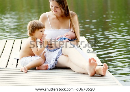 little boy kissing tiny foot of his newborn brother - outdoor shoot - stock photo