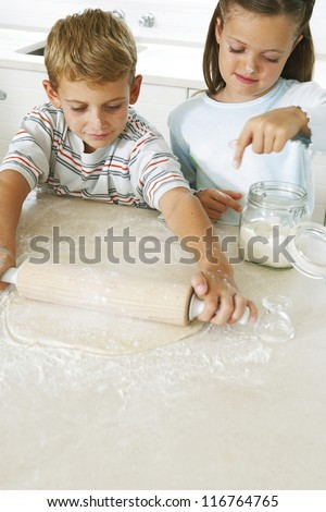 Little boy l rolling pastry in the kitchen with a rolling pin as his sister sprinkles fresh flour to prevent it sticking - stock photo