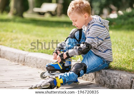 Little boy lace his roller skate sitting on the sidewalk - stock photo