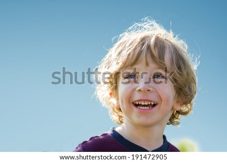 Little boy laughing in the sun. Close-up Portrait against blue sky. - stock photo