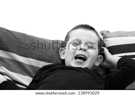 little boy laughing out oud on the sofa - stock photo