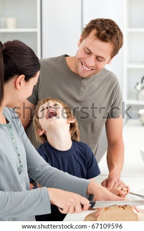 Little boy laughing while his mother cutting bread in the kitchen