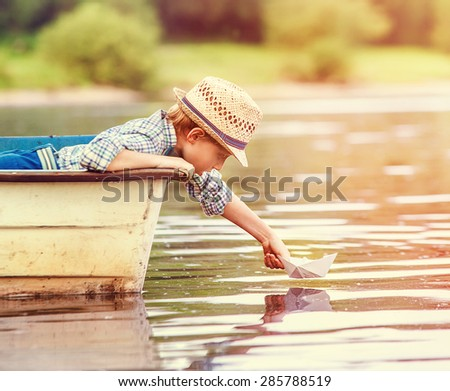 Little boy launch paper ship from old boat on the lake - stock photo