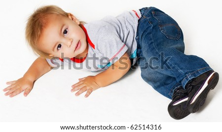 little boy laying down on a floor