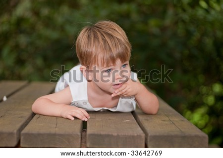 little boy laying on a picnic table with hand on chin - stock photo