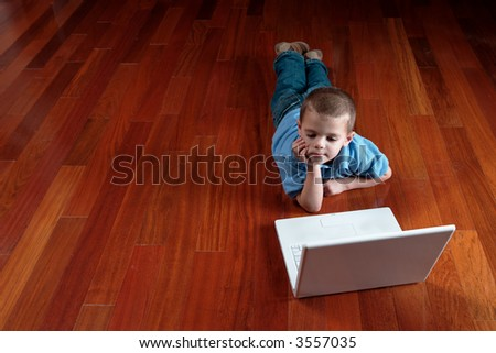 little boy laying on floor looking at a laptop computer