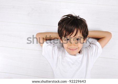 Little boy laying relaxed on white floor at home - stock photo