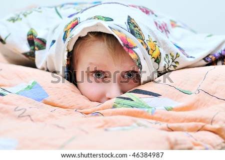 little boy laying under the pillow and watching something frightful on TV - stock photo