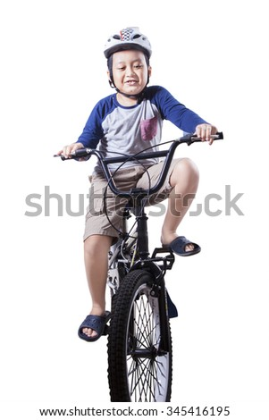 Little boy learn to ride a bicycle while wearing helmet, isolated on white background