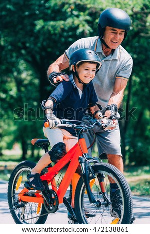 Little boy learning how to ride a bike