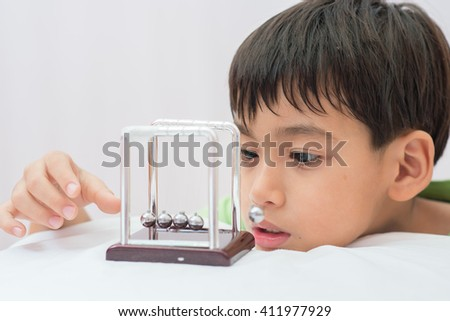 Little boy learning newton balance ball for science physic - stock photo