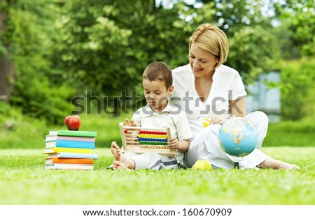 Little boy learning on abacus outdoors - stock photo