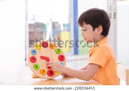 Little boy learning time with clock toy of Montessori  - stock photo
