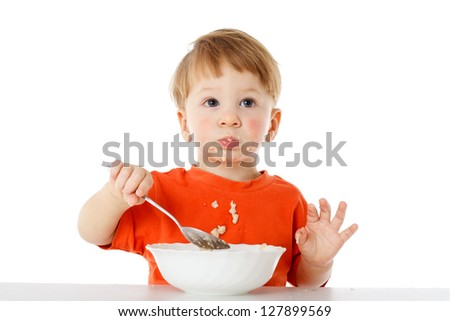 Little boy learning to feed herself - eating the oatmeal with a spoon from a bowl, isolated on white - stock photo