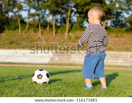 Little boy learning to play soccer taking careful aim before kicking the ball to a person just off frame