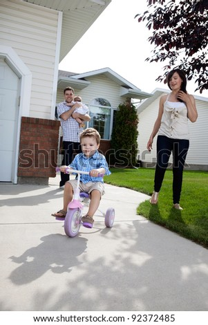 Little boy learning to ride tricycle while parents watch