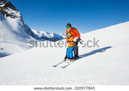 Little boy learns to ski on mountain resort with instructor helping to learn how to turn