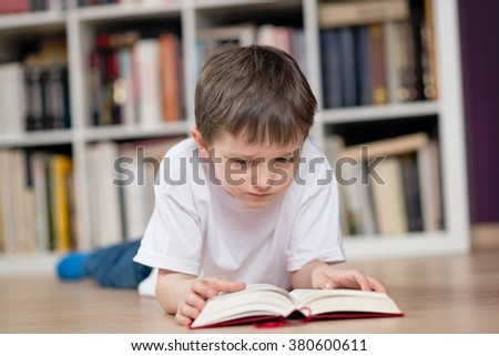 Little boy lies on his stomach and reading a book in the library. Dressed in a white t shirt and blue jeans