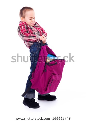 Little boy lifting big, heavy schoolbag full of books - stock photo