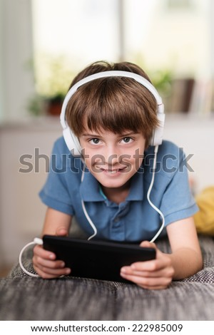 Little boy listening to music from his tablet on his headphones as he relaxes on his stomach on a sofa at home - stock photo