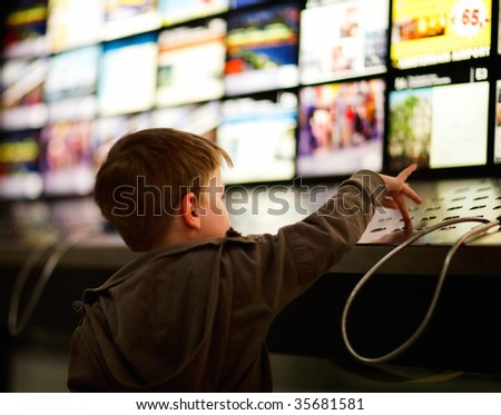 Little boy listening to music in store - stock photo