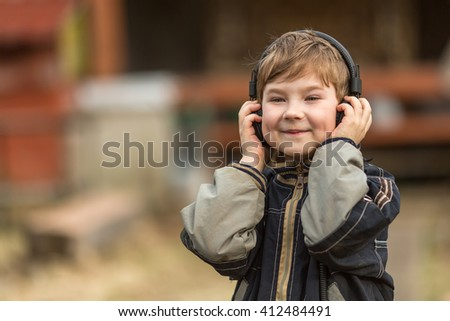 Little boy listening to music on headphones in the street, closeup portrait. - stock photo