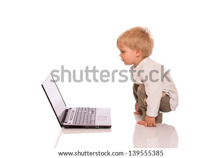 Little boy looking at a laptop. Isolated on white background - stock photo