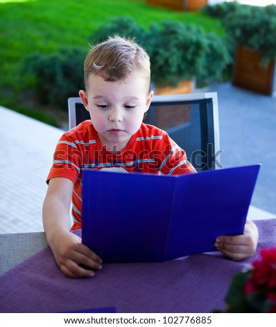 Little boy looking at a menu at a restaurant - stock photo