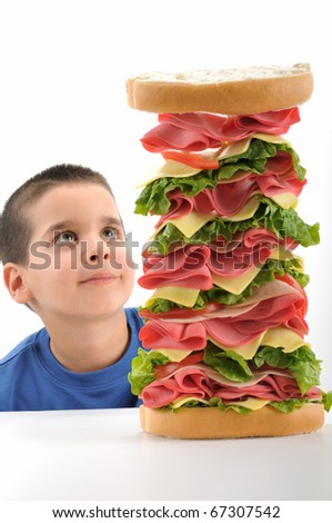 Little boy looking at big tower sandwich focused on sandwich isolated on white background.
