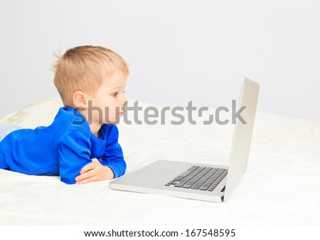 little boy looking at computer at home