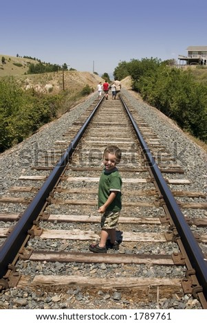Little Boy Looking at the Camera on the Train Tracks