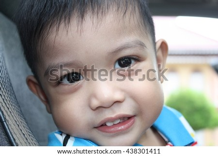Little boy looking at the camera, smiling and waiting someone coming at the car - stock photo