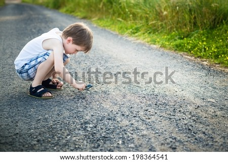 little boy looking at the stones lying on a dirt road through a magnifying glass - summertime - stock photo