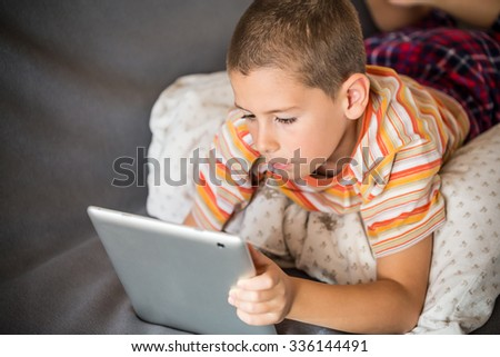 Little boy looking at touch pad - stock photo
