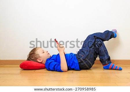little boy looking at touch pad at home - stock photo