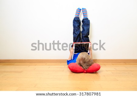 little boy looking at touch pad at home, early learning - stock photo