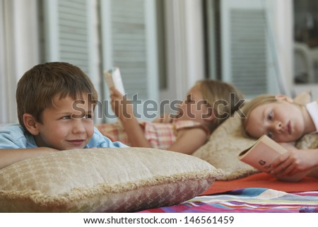 Little boy looking away while lying at porch with sisters reading books in background - stock photo