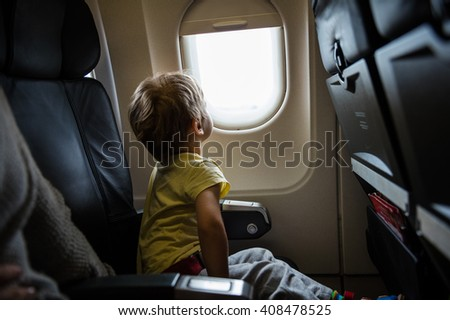 Little boy looking out of window in airplane - stock photo