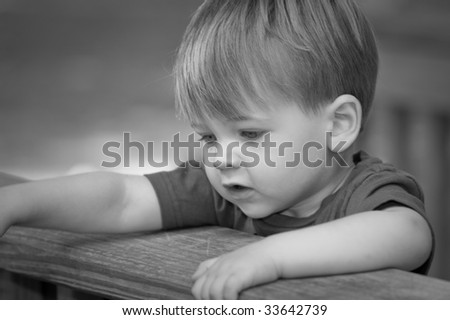 little boy looking serious with arms over deck railing in black and white - stock photo