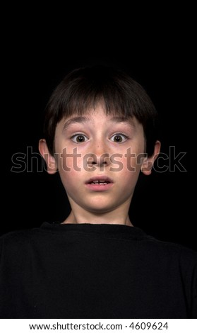 little boy looking surprised over black background