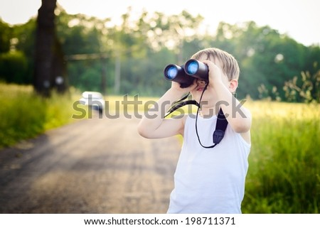 Little boy looking through binoculars while walking on a rural road - stock photo