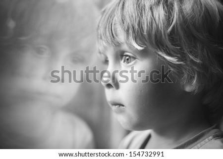 Little boy looking through window. - stock photo