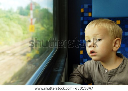 Little boy looking through window. He travels on a train. - stock photo