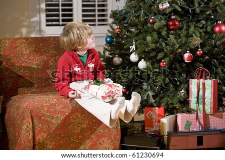 Little boy looking up at Christmas tree with present in lap