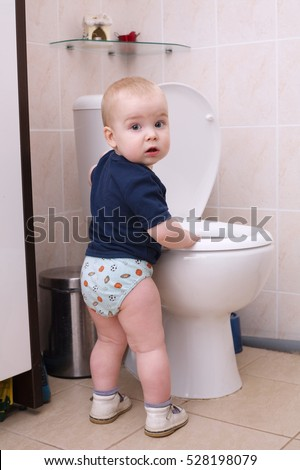 little boy looks in the toilet