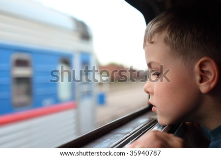 little boy looks in train`s window - stock photo