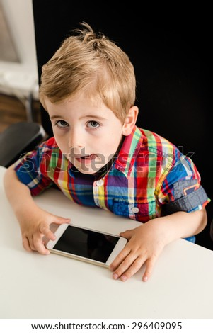 Little boy looks up while sitting on an office chair and playing with smartphone, showing his tongue reflects his concentration. The screen of the phone is blank and might easily be replaced with your - stock photo