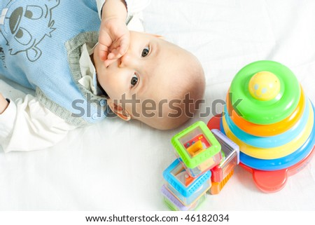 little boy lying down on the bed wis toys - stock photo